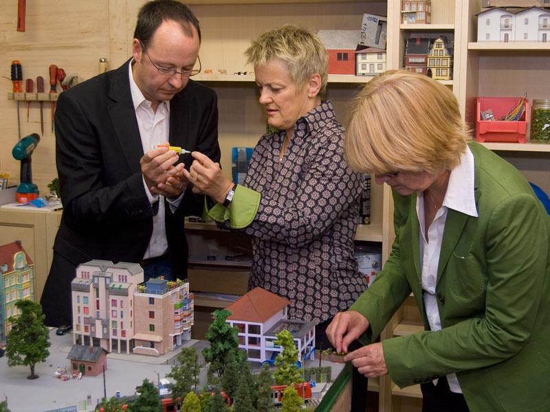 Zusammen mit Geschäftsführer Frederik Braun pflanzen Renate Künast und Krista Sager Sonnenblumen.